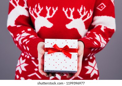 female wearing a red with white christmas jumper has a christmasgift in her hands