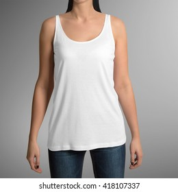 Female wearing white tank top shirt, isolated on gray background, with clipping path to change background