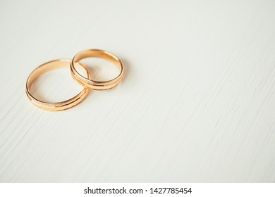 Female wedding frosted corrugated gold ring lie on male pair ring in the left part of white wooden background. Side view.