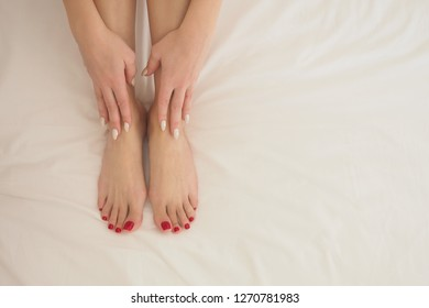 Female well groomed bare feet and hands on white bedding, close up. Woman put her fingers on her smooth skin. Skin care and massage concept.
