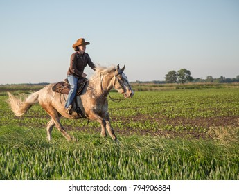 Female western style horse rider cowgirl. in evening sun and blue sky