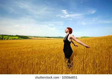 Female in wheat field enjoying summer