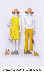 Female white clothing with sundress and yellow trousers ,straw hat, handbag on two mannequin isolated
