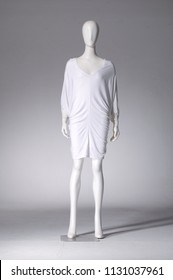 female in white sundress on full mannequin-gray background