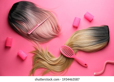 Female wigs, brush, comb and curlers on color background