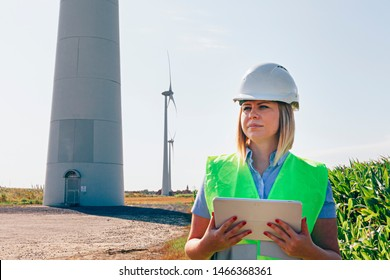 female wind engineer checking a tablet in a turbines field. renewable energy and job technology concept