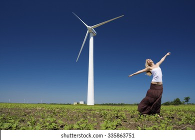 Female at wind power generator turbine - alternative and green energy source