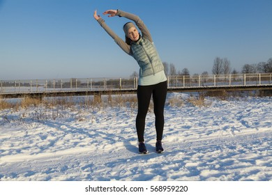 Female in winter after jogging in snow with blue sky, stretching