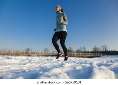Female in winter jogging in snow from right to left