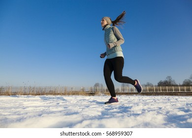 Female in winter jogging in snow from right to left with copy space