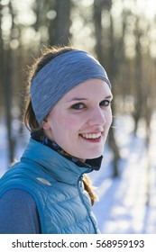 Female in winter, Portrait after jogging in snow, trees in background and back light