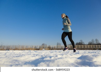 Female in winter while jogging ight to left in snow with blue sky