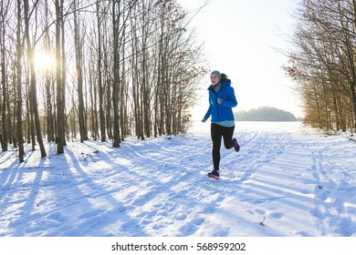 Female in winter while jogging in snow, trees in background