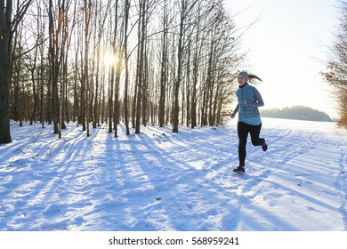 Female in winter while jogging in snow, back light and trees in background