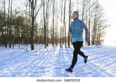 Female in winter while jogging in snow, trees in background and back light