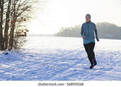 Female in winter while jogging in snow, trees on the left