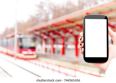 Female / woman / girl hand with mockup smartphone / mobile phone with red tram and public transport station on background in winter