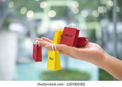 Female woman hand hold shopping bag, female happy time on the day mid year sale. Business sales increase revenue shares concept