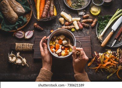 Female woman hands holding pan with diced colorful vegetables and a spoon on rustic kitchen table with vegetarian cooking ingredients and tools. Healthy and clean food  cooking and eating  concept.