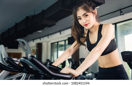 Female woman lifestyle using equipment machine exercise bike for training cardio workout at fitness gym