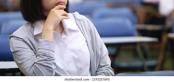 The female woman and rest one's chin on one's hand in the class with blur background, in concept of education, concentration, university.