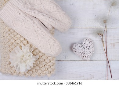 Female woman warm knit Scarf Neck warmer Circle Cowl and mittens on white wooden rustic background. Cozy winter. Romantic female fashion style accessories background. Warmth concept,flat lay