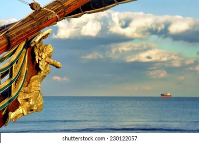 Female Wooden Carved Figurehead found at the Prow of Old Ship. Modern ship at sea horizon.