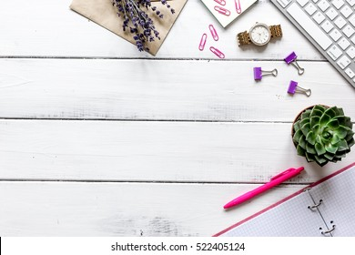 female wooden desktop with flowers top view