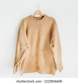 Female woolen sweater on hanger at white wall. Woman fashion clothes concept.