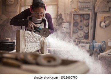 Female worker in an art workshop, grinding a piece of white marble, sculptor creating a stone sculpture, cloud of dust flying away, stonemasonry and stonecraft