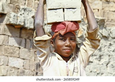 Female worker carry bricks on her head