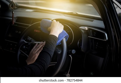 Female worker cleaning car dashboard, vintage color tone