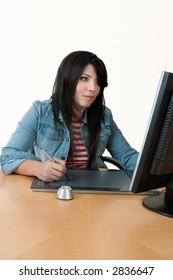 A female worker at computer with graphic tablet.