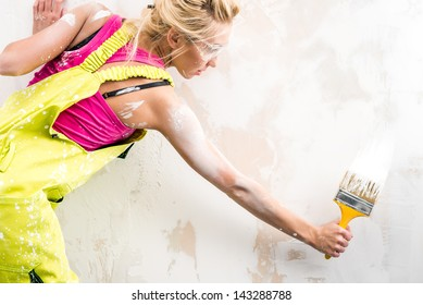 Female worker in coverall paint a  wall
