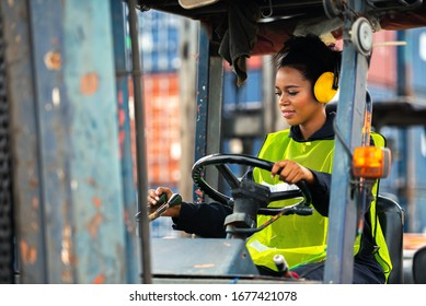 Female worker driving forklift in industrial container warehouse.