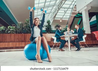 Female worker exercising on fitness ball in office.