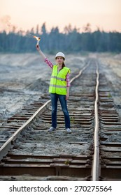 female worker lights signal torch on rails