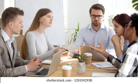Female worker listen attentively to colleague at business meeting with boss. Group of people discuss work with manager in office. Office workers discuss business, argue, exchange ideas, make remark