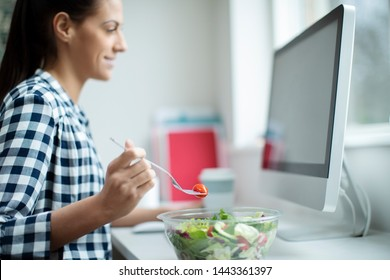 Female Worker In Office Having Healthy Salad Lunch At Desk