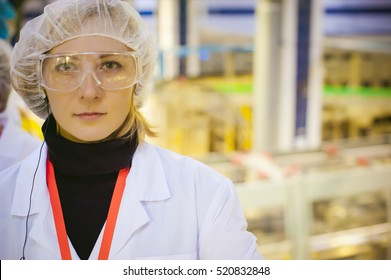Female worker on the production line of beer factory. portrait of a woman in a white robe, standing on the background of the production line at the factory bottling of finished products