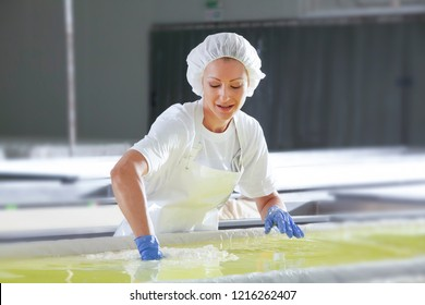 Female worker on white feta cheese production line