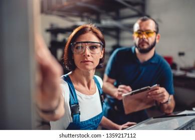 Female worker operate CNC machine while supervisor monitoring procedure