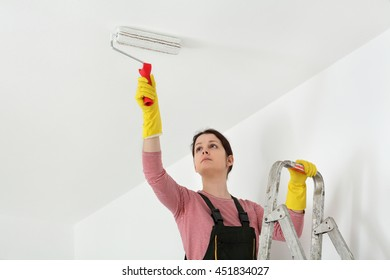 Female worker painting ceiling with paint roller from ladder