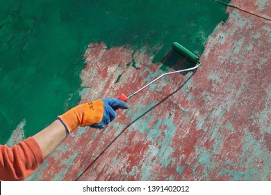 Female worker painting old metal roof plate to green color using paint roller, closeup of hand with tool