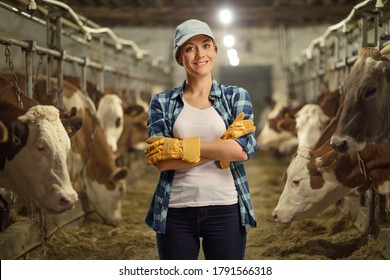 Female worker posing on a cow dairy farm inside a cowshed