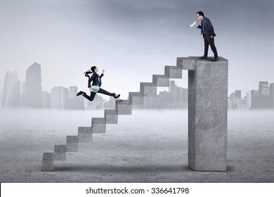 Female worker run on the stair to meet with her leader on the top bar