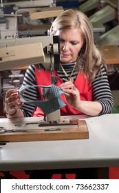 Weibliche Arbeiter nähen Leder in einer Schuhfabrik