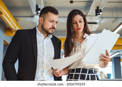 Female worker showing papers to her serious boss in the lobby