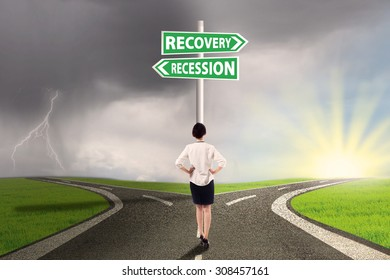 Female worker standing on the road and look at the signpost pointing on the road to recovery or recession finance