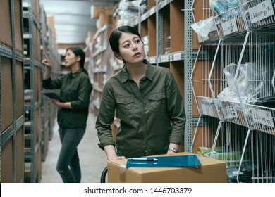 female worker in warehouse pushing cart with cardboard boxes. young woman staff putting clipboard on parcels and finding empty shelf to place goods. bokeh view of girl coworker doing stocktaking.